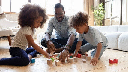 Obraz Happy millennial dad enjoying learning playtime with sibling preschooler kids on warm floor. Daddy and cute children playing games wit wooden toy building blocks, improving skills. - fototapety do salonu