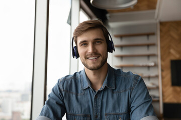 Headshot portrait of smiling young Caucasian man in earphones talk speak on video call online with...