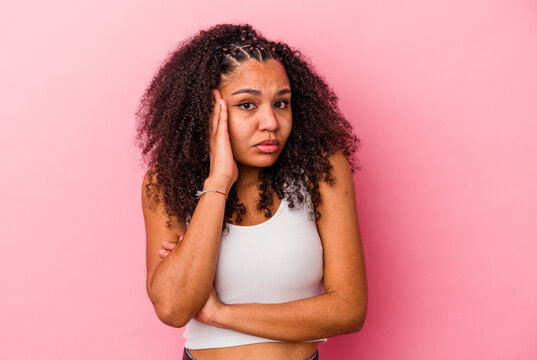 Young african american woman isolated on pink background blows cheeks, has tired expression. Facial expression concept.