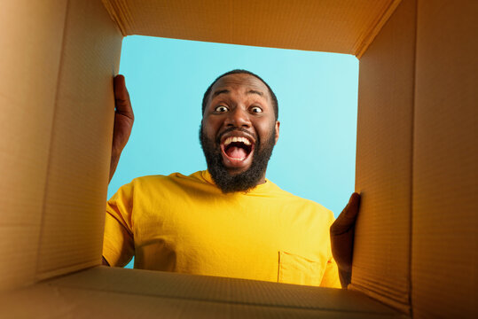 Happy man receives a package from online shop order. happy and surprised expression. cyan background.