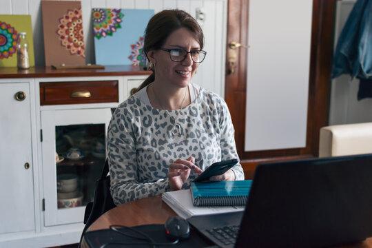 Mujer de negocios trabajando feliz desde casa con teléfono celular y  computadora portátil en período de aislamiento