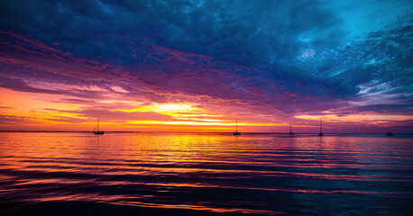 Sunset or sunrise in ocean, nature landscape background, pink clouds flying in sky to shining sun. Evening or morning view.