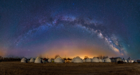 The milky way and Mongolia yurts in grassland.