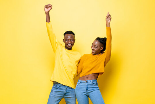 Happy fun smiling young African American couple holding each other and raising hands up in the air on yellow isolated studio background