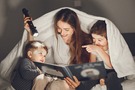 Mom and child reading a book with a flashlight