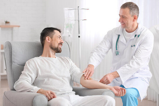 Doctor and man undergoing course of chemotherapy in clinic. Prostate cancer awareness concept