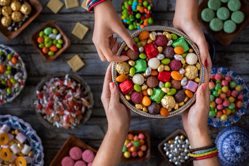 Bowl of candies and chocolate at the hands of two women. Kız isteme ve şeker bayramı ikramı
