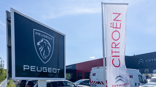 Peugeot citroen brand logo on flag panel station with dealership sign text shop of French automobile garage