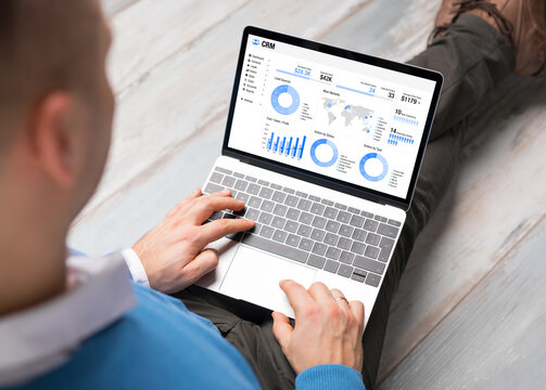 Man using CRM software on laptop with different graphs and charts showing sales data for his business