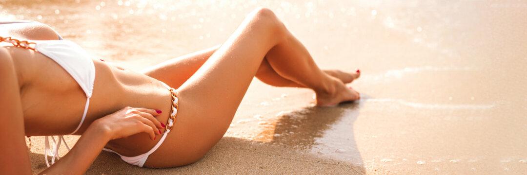 Woman in white bikini sunbathing on the beach
