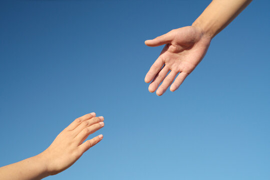 Close-up of hands drawn to each other on blue background, friendship, help