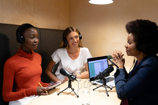 Diverse group of happy female business colleagues wearing headphones, speaking to microphones