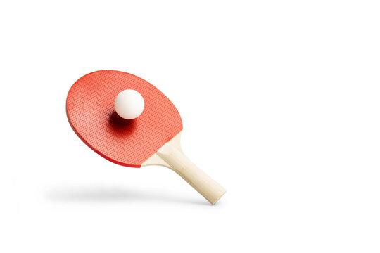 Raqueta de ping-pong con una pelota levitando sobre un fondo blanco liso y aislado. Vista de frente. Copy space. Concepto: Deportes