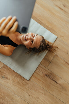 Top view of a happy woman lying on the floor and using tablet.