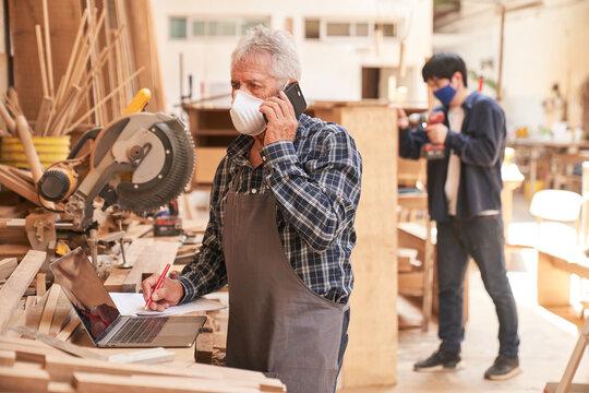 Senior Handwerker mit Maske am Telefon