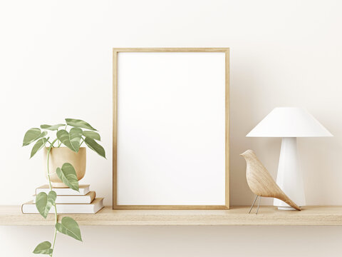 Small vertical wooden frame mockup in japandi style interior with trailing green plant in pot, lamp, books and shelf on empty warm white wall background. A4, A3 format. 3d rendering, illustration
