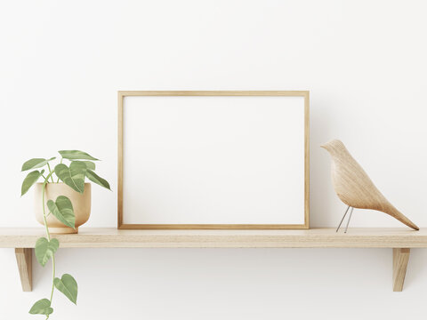 Small horizontal wooden frame mockup in scandi style interior with trailing green plant in pot, bird and shelf on empty neutral white wall background. A4, A3 format. 3d rendering, illustration
