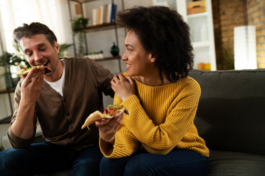 Cheerful young couple sitting on sofa at home. Happy woman and man eating pizza while watching a movie..