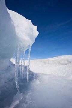 Symmetrical icicles with ice ledge and blue sky on  Baikal