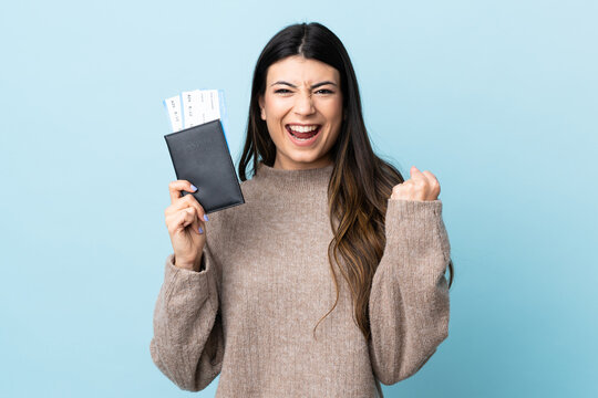 Young brunette girl over isolated blue background happy in vacation with passport and plane tickets