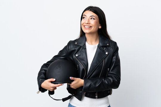 Young woman holding a motorcycle helmet over isolated white background laughing