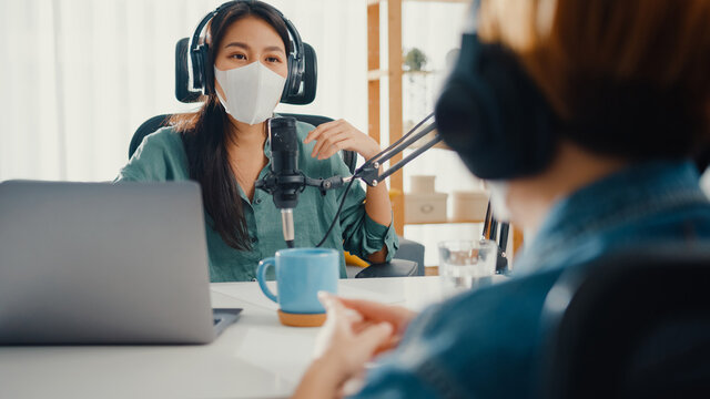 Asia girl radio host record podcast use microphone wear headphone interview guest content wear mask protect virus conversation talk and listen in her room. Podcast from home, coronavirus quarantine.