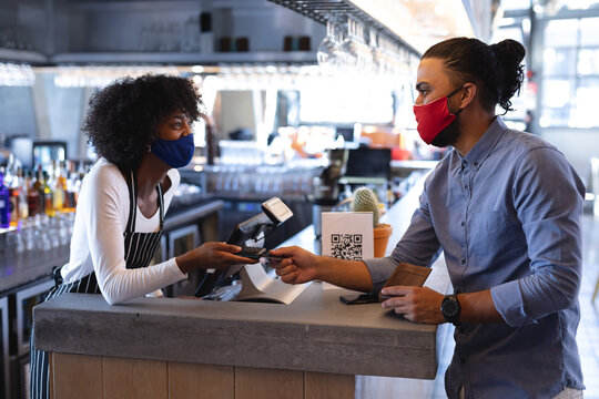 Diverse male and female waiters wearing face masks, using payment terminal in cafe