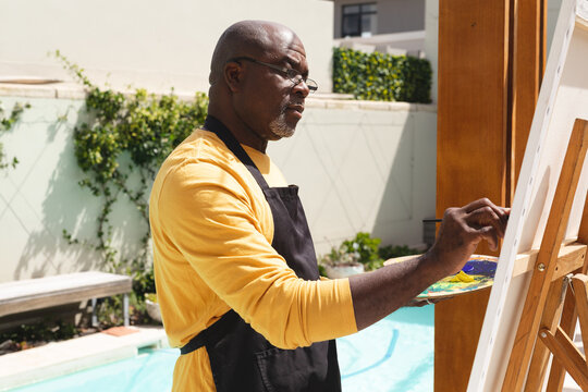 African american senior man wearing apron painting on canvas near the pool
