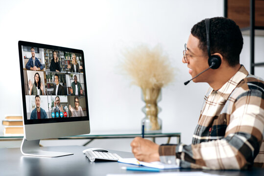 Side view of mixed race guy with headset, sitting at a desk, talking on video conference with business partners, different successful people on the computer screen, discussing strategy by video call