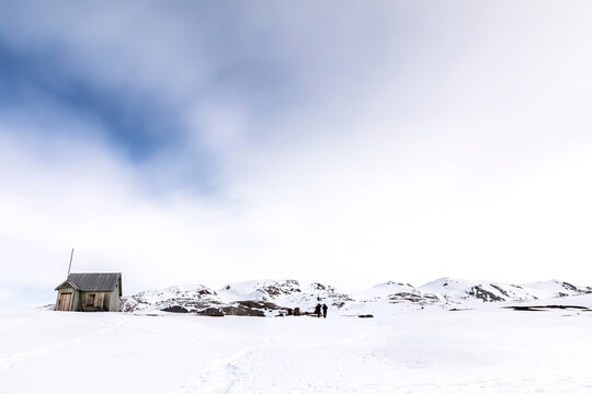 Abandoned cabin and marble mine at Camp Mansfield, New London, Svalbard. Snowy mountain scene with photographers capturing the landscape.