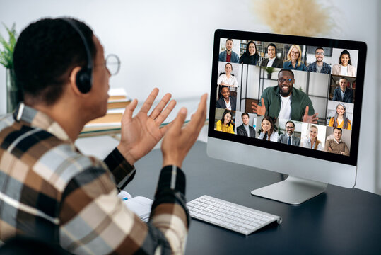 Video call, online conference. Over shoulder view of mixed race man, on computer screen with multinational group of successful business people, virtual business meeting, telecommunication concept