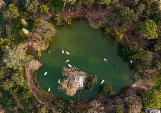 Aerial view of small boats in a small lake in public garden near Esculapio temple, Rome, Lazio, Italy.