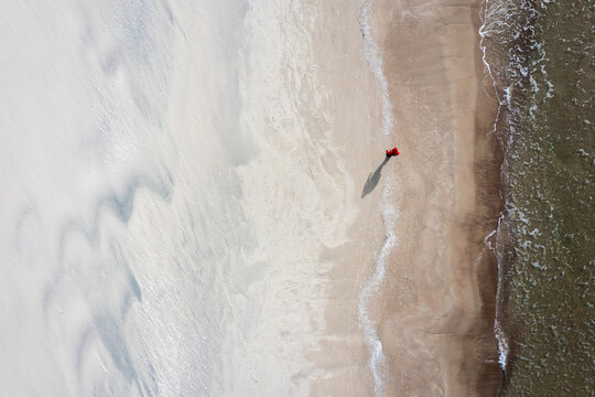 Aerial view of a person walking on the beach near Baltic sea in Klaipeda, Lithuania.