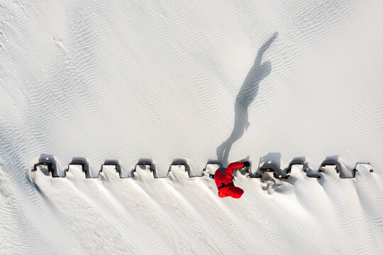 Aerial view of man silhouette shadow balancing on the metal construction in beach, Klaipeda, Lithuania.