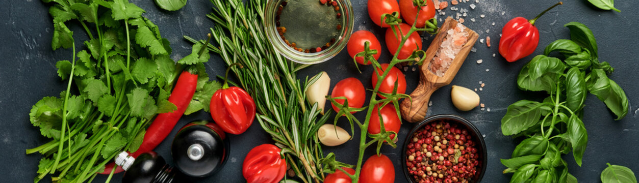 Food cooking background. Fresh rosemary, cilantro, basil, cherry tomatoes, peppers and olive oil, spices herbs and vegetables at black slate table. Bannr top view.