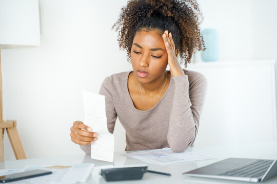 Woman holding paper bill, paying for gas, electricity and rent