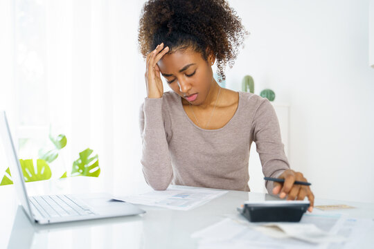 Unhappy black woman feel stressed working on computer at home