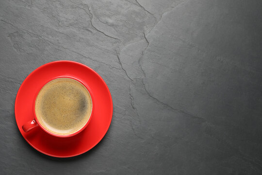 Aromatic coffee in red cup on black background, top view. Space for text