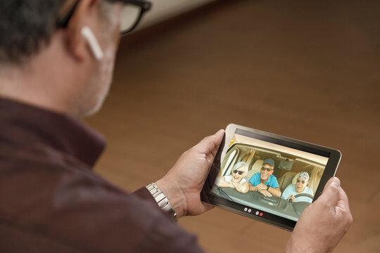 Tablet tenuto in mano da un uomo , nel cui schermo compaiono tre signori anziani  in remoto in che si collegano alla guida di un camper