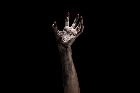 Creepy bloody zombie hand over dark background with clipping path. Horror and Halloween theme.