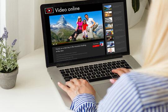 Woman watching videos online on laptop