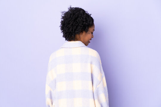 Young African American woman isolated on purple background in back position and looking side