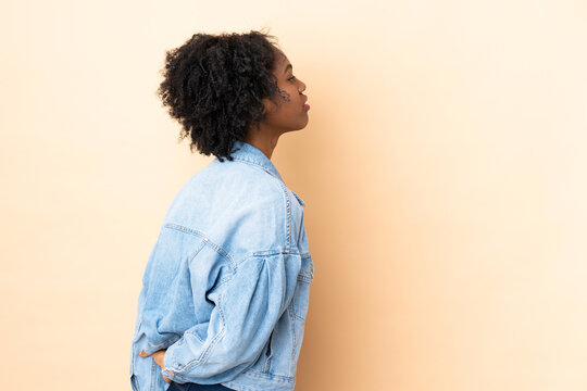 Young African American woman isolated on beige background in back position and looking back