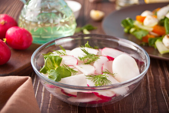 Spring fresh salad with radish and basil on the dinner table