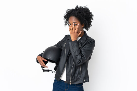 Young African American woman with a motorcycle helmet isolated on white background covering eyes and looking through fingers