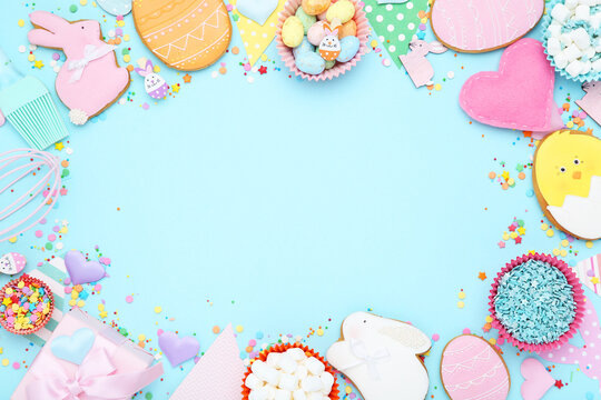 Easter gingerbread cookies with colorful eggs, gift box and sprinkles on blue background