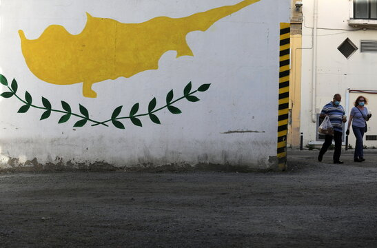 People wearing protective masks walk next to a Cypriot flag painted on a wall in capital Nicosia,
