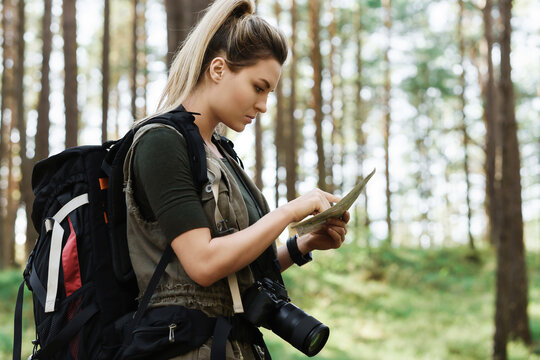Female hiker with big backpack using map for orienteering in the forest