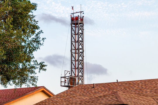 Coral Springs, Florida, USA - April 27, 2021: North Springs Improvement operating noisy, ground shaking, pool home damaging, ugly deep injection waste water well construction tower in Westview Estates