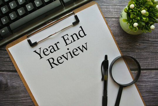 Selective focus of pen , magnify glasses and notebook written with Year End Review on white wooden background.